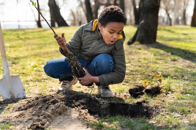 Ребенок учится сажать дерево
