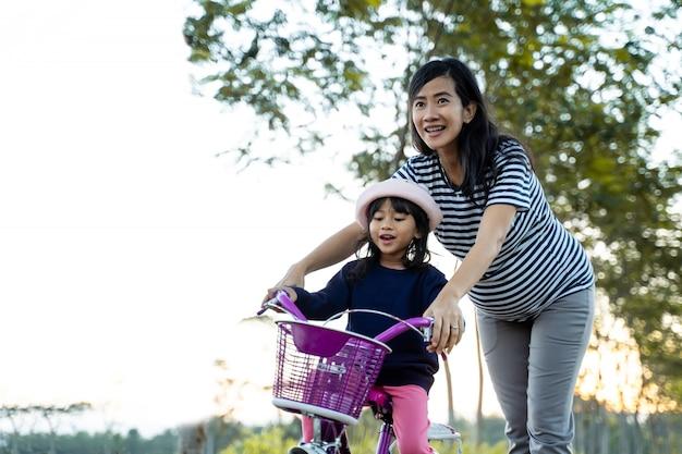 子供が母親と一緒に自転車に乗ることを学ぶ