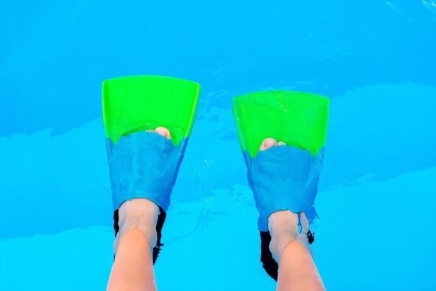 푸른 물 배경 위에 수영 오리발을 가진 아이 다리. 물에 오리발. 다이버 지느러미. 수영장에서 지느러미에 수중 아이 다리, 평면도. 복사 공간이 있는 모형.