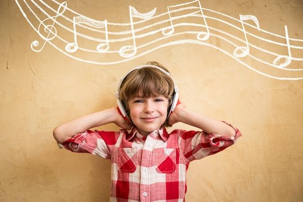 Малыш слушает музыку дома. хипстерский ребенок с наушниками. концепция ретро музыки