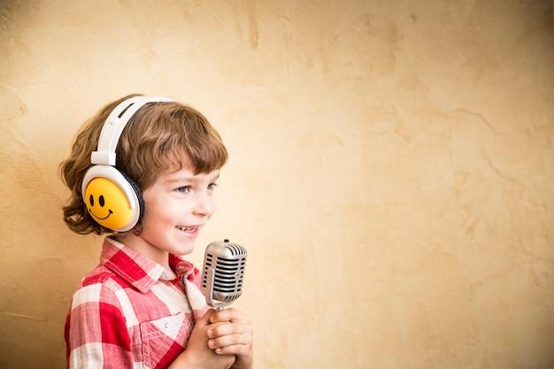 Малыш слушает музыку дома. хипстерский ребенок с ретро винтаж микрофоном