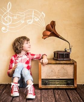 Малыш слушает музыку дома. хипстерский ребенок с ретро винтаж радио