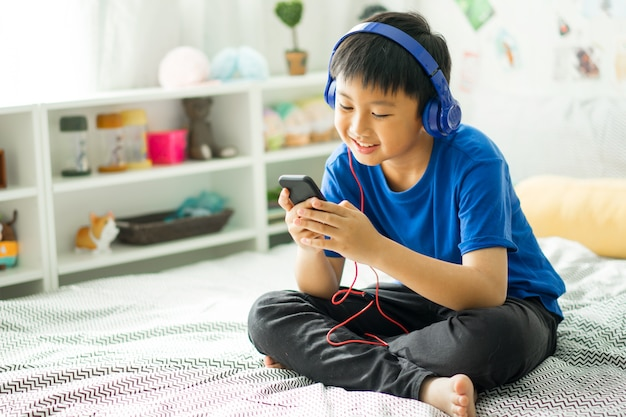 Kid listening to music on bed at bedroom for relax