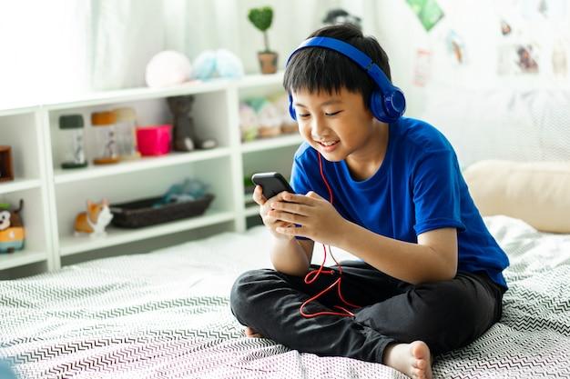 Малыш слушает музыку на кровати в спальне для отдыха