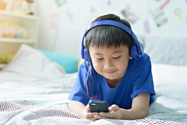 Малыш слушает музыку на кровати в спальне