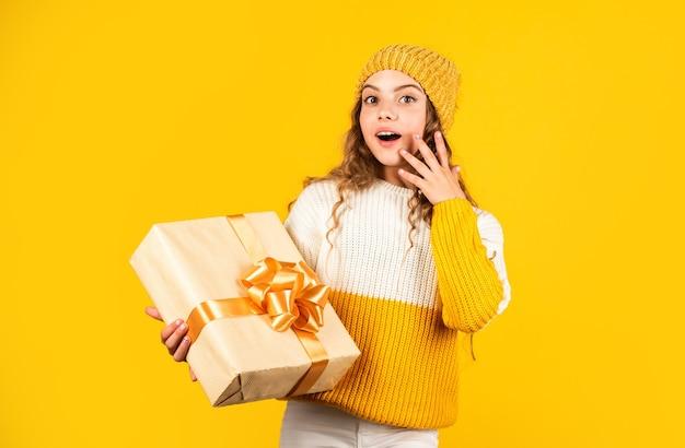 어린 소녀는 노란색 배경에 리본이 달린 선물 상자를 들고 있습니다. 십 대 소녀는 휴가 선물을 받았습니다. 최고의 크리스마스 선물. 아이 흥분 포장 풀기 선물. 딸을 위한 크리스마스 선물. 놀라움을 즐기십시오.