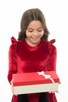 우아한 드레스 곱슬 헤어스타일의 어린 소녀는 선물 상자를 들고 있습니다. 선물을 풀면서 신이 난 아이. 작고 귀여운 소녀가 명절 선물을 받았습니다. 안에 있는 것. 아이들을 위한 최고의 장난감과 크리스마스 선물.