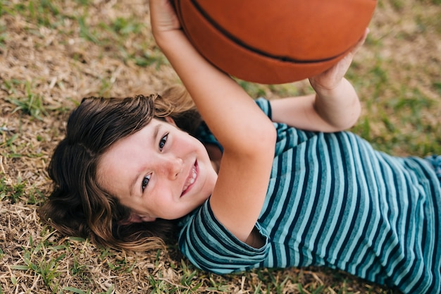 Kid lying on grass and holding ball