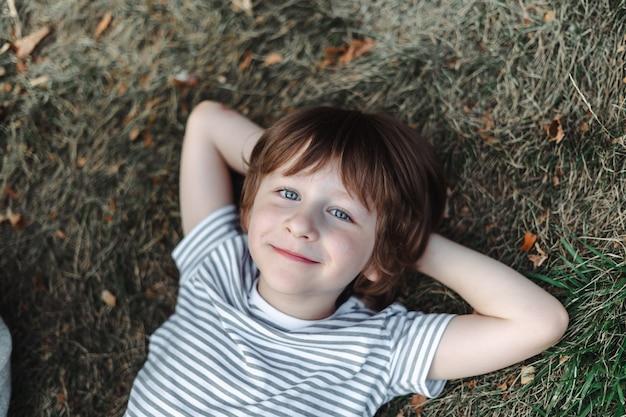 Ребенок лежит на спине в траве в парке. мальчик отдыхает на зеленой лужайке. ребенок отдыхает на улице.