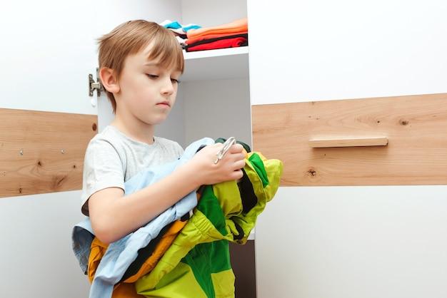 Малыш наводит порядок в своем гардеробе дома. ребенок собирает одежду в шкафу.