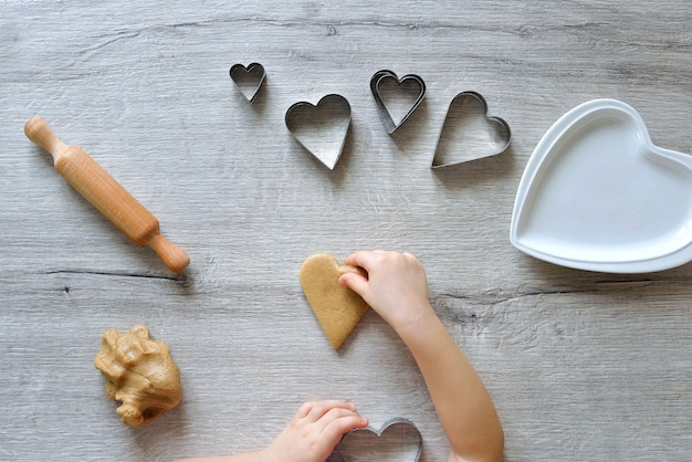 Малыш делает пряники в форме сердца.