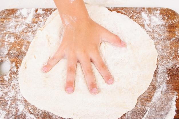 生の生地のクローズアップに手形を作る子供