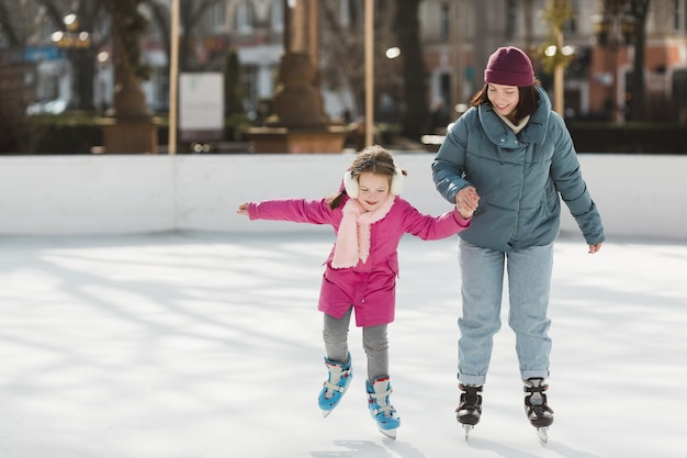 Kid and mother ice skating together