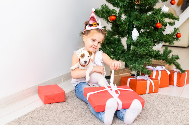 Kid opening xmas presents. child under christmas tree with gift boxes.