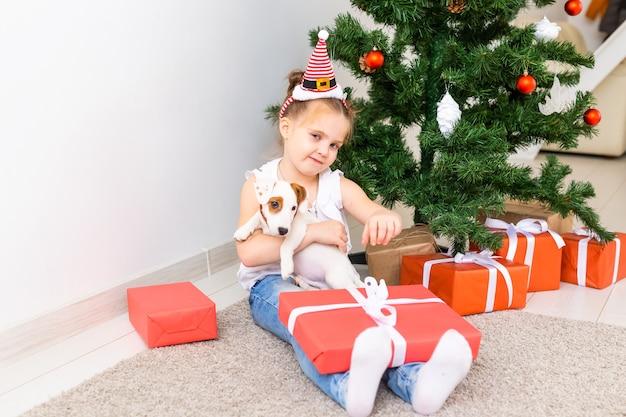 Детские открытия рождественские подарки. ребенок под елкой с подарочными коробками.