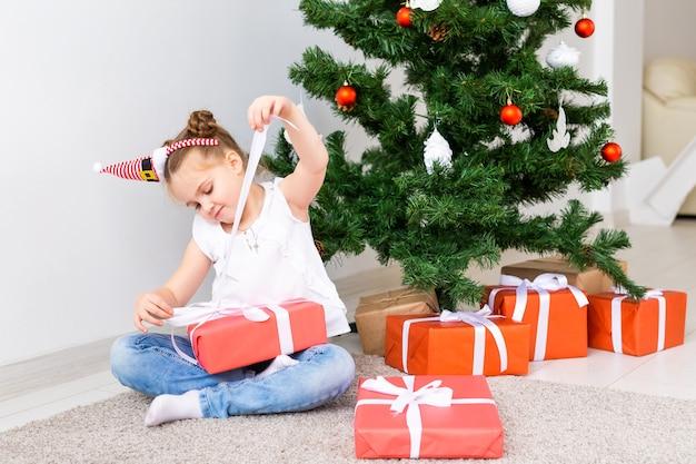 キッドオープニングクリスマスプレゼント。ギフトボックスとクリスマスツリーの下の子。