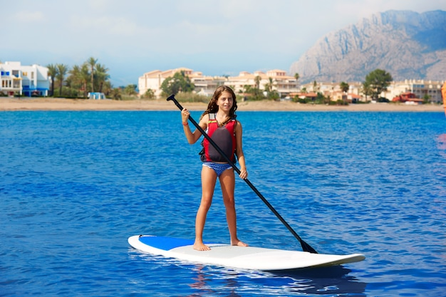 Kid paddle surf surfer girl with row in the beach