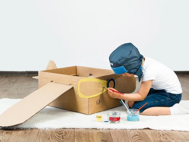 Kid painting cardboard boat