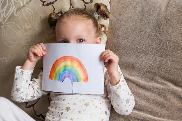 Малыш рисует радугу во время covid-19. девушка держит рисунок с радуги. оставайся дома кампания по борьбе с коронавирусом в социальных сетях, все будет хорошо, надежда во время пандемии