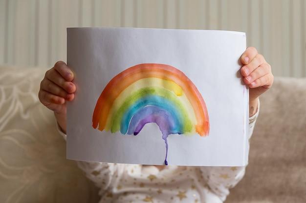 Малыш рисует радугу во время covid-19. девушка держит adrawing с радугой. оставайся дома кампания по борьбе с коронавирусом в социальных сетях, все будет хорошо, надежда во время пандемии