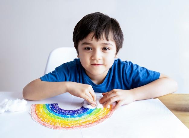 白い紙の上の子供の絵の虹。虹の雲の装飾的な要素としてのdiyコットンウール。子供は家にいます
