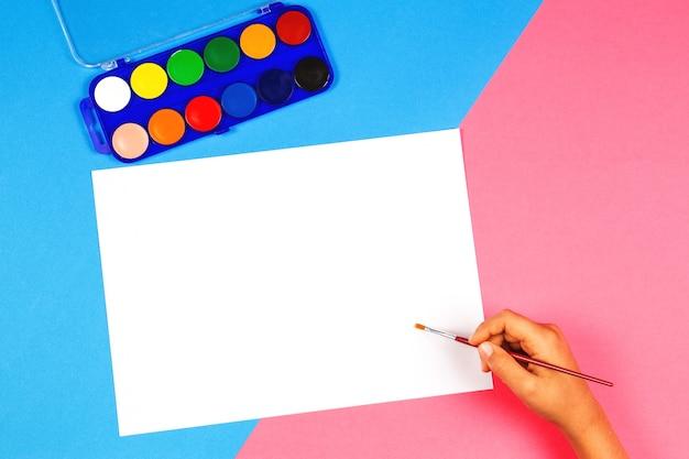 Ребенок рисует кистью и красочными акварельными красками