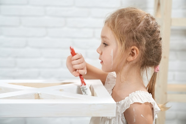 Kid painting wooden furniture with brush and white color