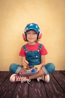 Малыш-пилот играет дома. концепция успеха и инноваций