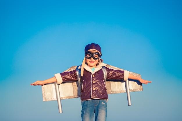 푸른 겨울 하늘 배경에 장난감 제트 팩을 든 아이 조종사. 야외에서 노는 행복한 아이
