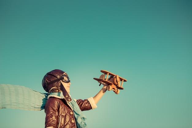 가을 하늘 배경에 장난감 나무 비행기와 아이 조종사 야외에서 노는 행복한 아이