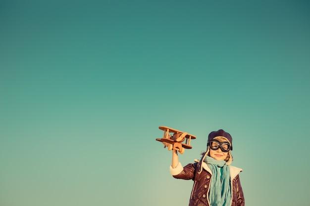 가을 하늘 배경에 장난감 나무 비행기를 가진 아이 조종사 행복한 아이 야외에서 노는