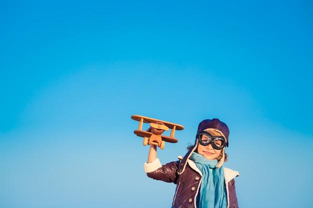푸른 겨울 하늘 배경에 장난감 나무 비행기를 가진 아이 조종사. 야외에서 노는 행복한 아이