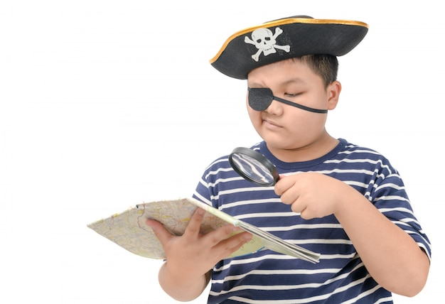 Kid pirate using magnifying glass to view the map