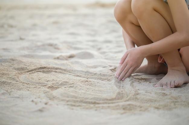 해변에서 모래를 가지고 노는 아이, 야외 일몰 저녁 시간을 노는 어린 소녀