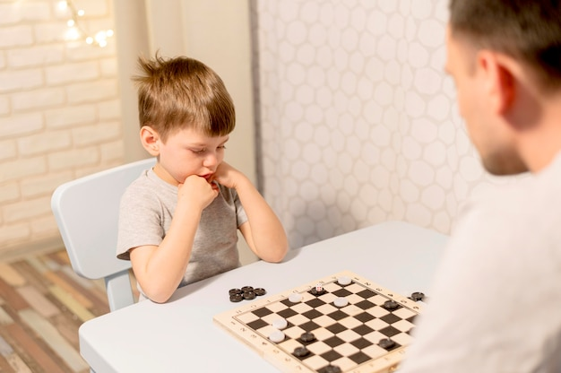Kid playing chess with father