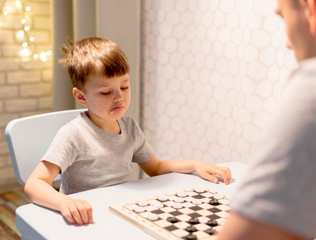 Kid playing chess with man