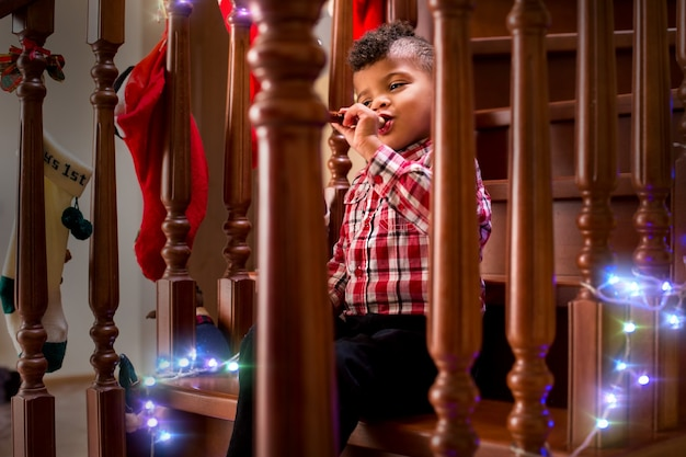 Ребенок играет на флейте на лестнице мальчик с флейтой на рождество на все хорошее, музыка всегда приносит радость