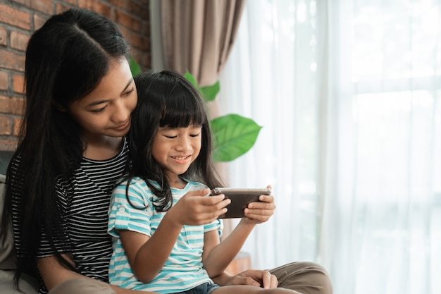 Kid playing game with sister on smart phone