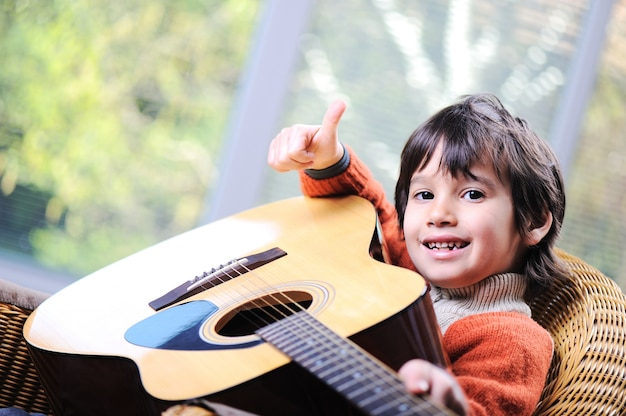 Kid playing guitar at home