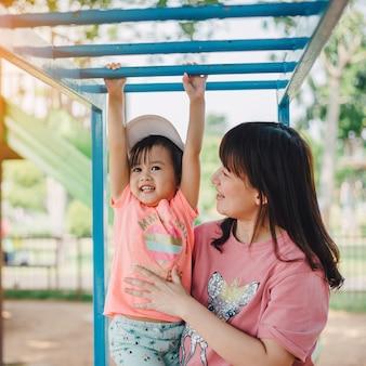 母と遊び場で遊ぶ子供