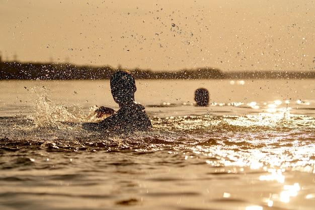 水で遊ぶ子供。川の少年の周りに水しぶきが。美しい夕日。夏休みと子供の頃のコンセプト。閉じる。