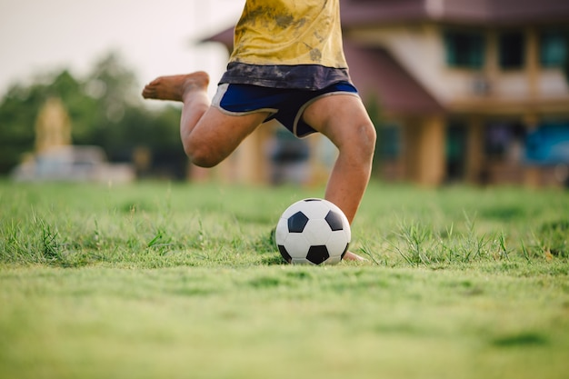 Kid playing soccer football for exercise