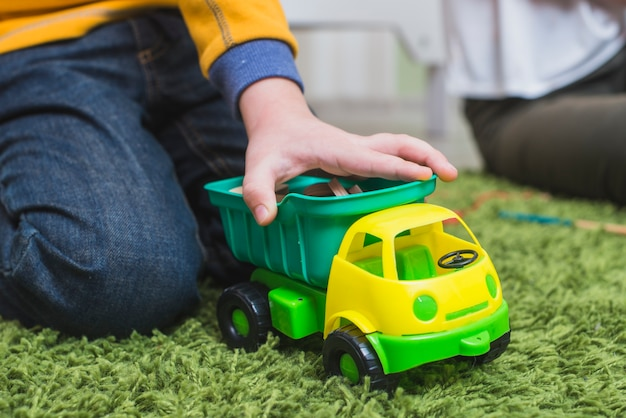 Kid playing toy car on floor