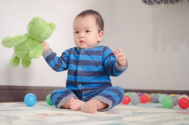 Ребенок играет с мячами и зеленым плюшевым мишкой на мягком ковре