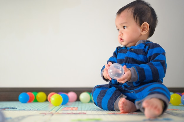 Kid playing with balls on soft carpet