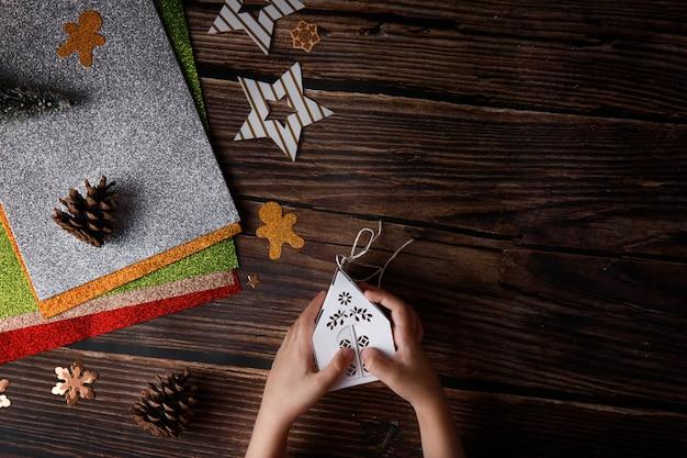 나무 배경에 크리스마스 공예품을 가지고 노는 아이. 테이블에 휴일 항목.
