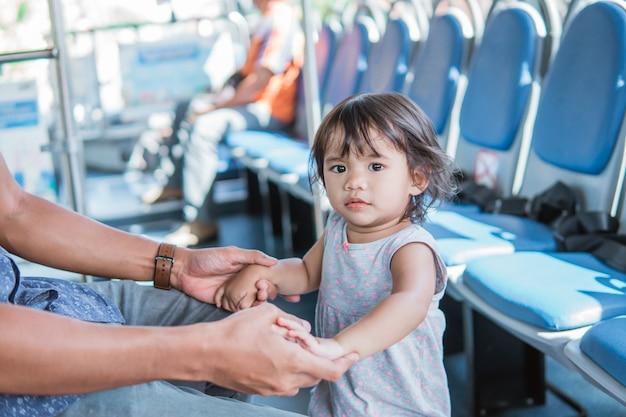 公共交通機関の中でお父さんと遊ぶ子供