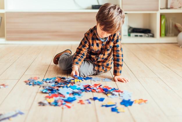 Kid playing with jigsaw