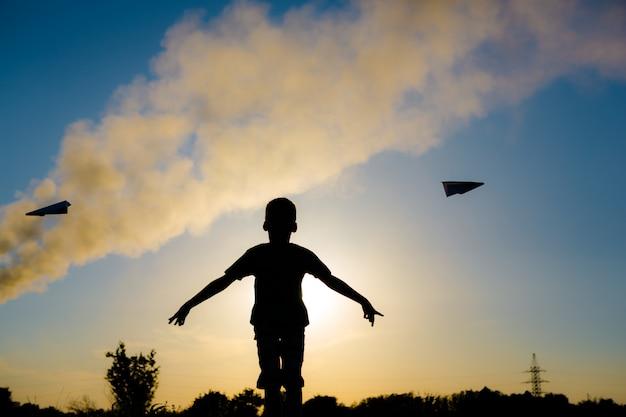 석양에 종이 비행기를 가지고 노는 아이