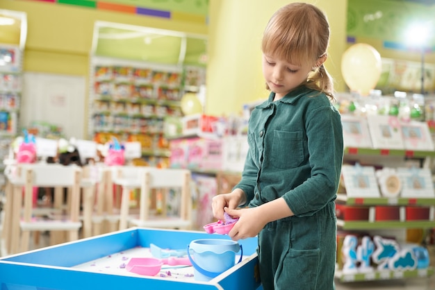 Kid playing with small sandbox and set of toys in shop.